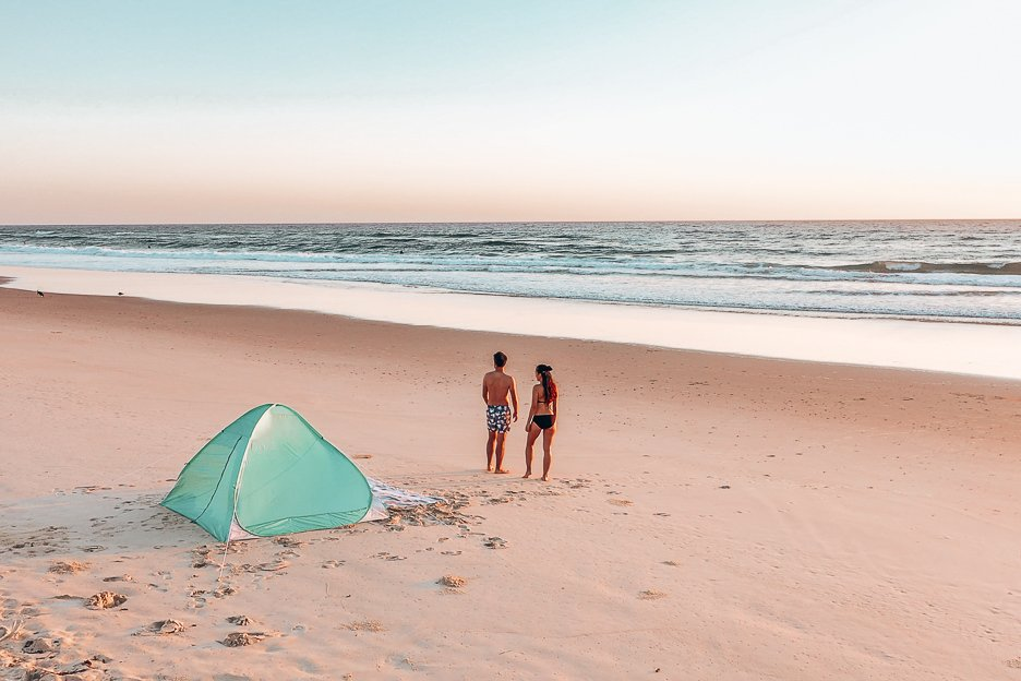 A couple stand on the sand next to an Oz Trail Beach Shade on Palm Beach at sunrise, Queensland, Australia