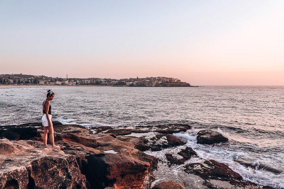 A girl stands on the rocks of Bondi Beach with a peachy sunrise on the horizon, Bondi Beach, New South Wales, Australia