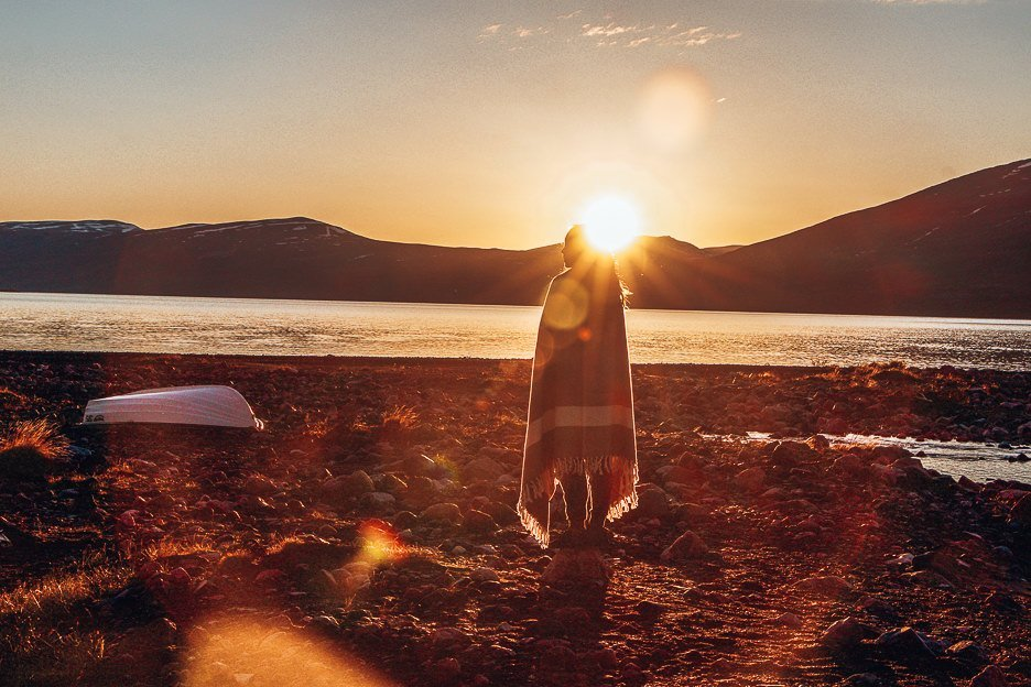 Jasmine stands on the shoreline in Swedish Lapland with a blanket wrapped around her during sunset, Sweden