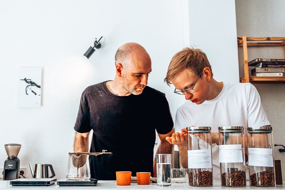 Two male baristas examine coffee beans in Crooked Nose & Coffee Stories cafe in Vilnius, Lithuania