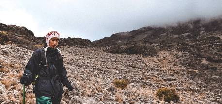 A girl navigates the rocky trail on the Machame Route on Mt Kilimanjaro