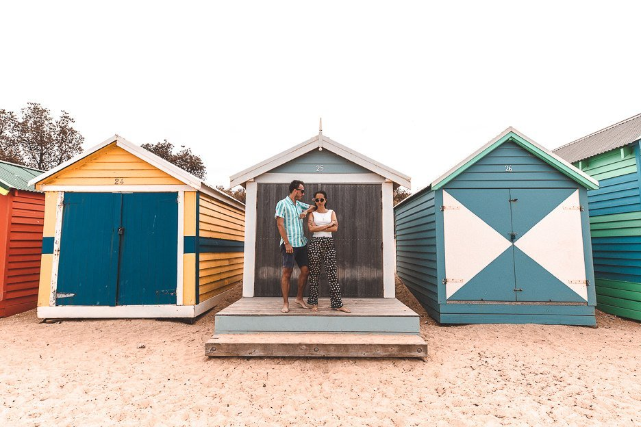 A couple pose in front one of the Brighton Bathing Boxes, Melbourne Victoria