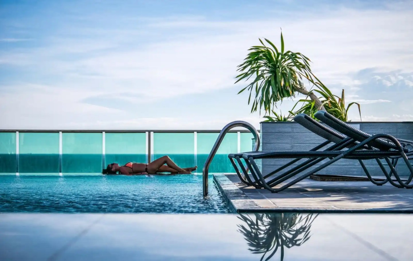 Picture of woman lying by hotel pool