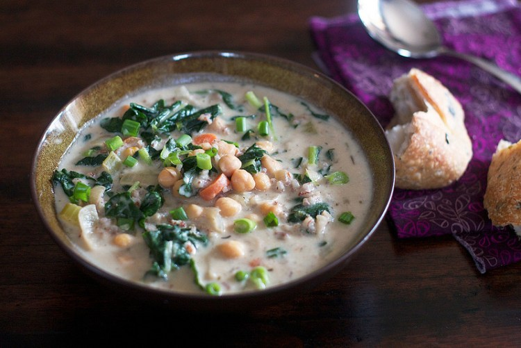 image of a bowl of vegan creamy chickpea and rice soup with kale