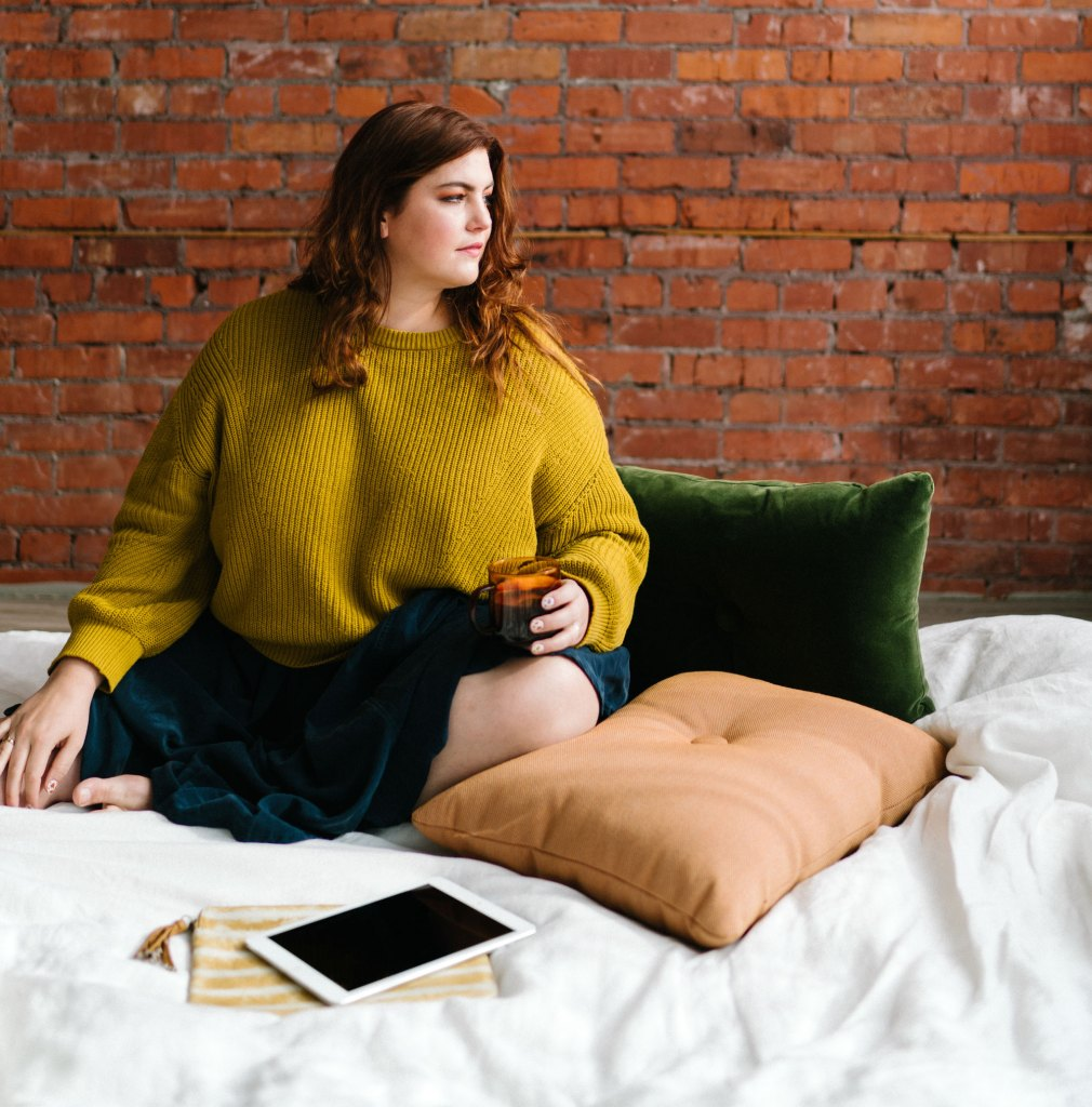 How to overcome crippling self doubt in business. A woman sits on a bed in front of a red brick wall.