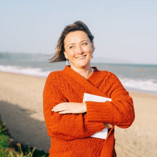 Claire Collis Writer and Digital Education Specialist stood on a beach