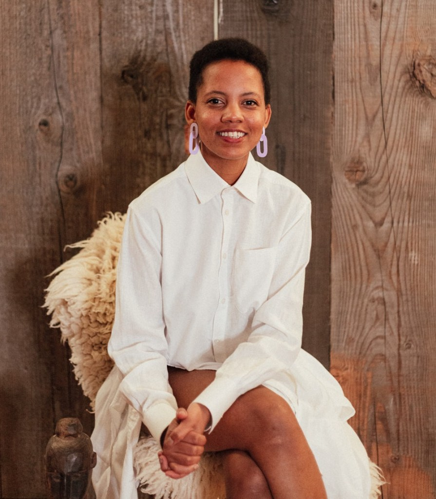 Samantha Moyo sat cross legged on a stool covered in a sheepskin
