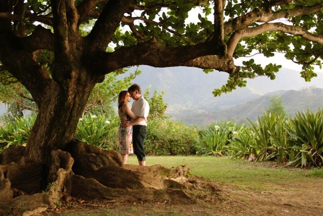 Couple posing under tree in Kauai's lush green landscape near Hanalei Bay