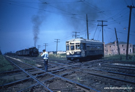 """One of our readers writes, """"the 141 crossing the IHB tracks at Oak Street in LaGrange Park. The car is headed westbound, the train is southbound, possibly entering the sidings that are just south of Oak. The Trolley turned south and paralleled the IHB down to the CB&Q tracks where it turned west along Hillgrove. The home under construction in the background is the second or third house north of Oak on the west side of Beach. """""""