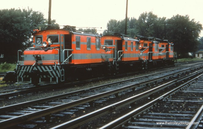 """#13 - WS: Wow! Rare shot of four of the freight locos (the 2000s and 3000s), all in the same paint job. Believe this is on the freight lead (located south of freight yard and west of the two main tracks of Aurora Branch) in front of Wheaton Shop. View looking S/E. EM: North yard of the Wheaton Shops, with 3004, 3003, 2001, and 2002 lined up. AK: Two closest are the ex Oklahoma Ry motors. EM: The two closest locomotives were built by Baldwin-Westinghouse. The two more distant ones were built by GE. The ex-Oklahoma Ry locomotives were numbered 4005 and 4006 and are not in the picture. Bob Campbell: """"Regarding photo #13, in CERA Bulletin #105, page IV-9, the Wheaton map indicates that the four freight motors are sitting on the """"passing siding"""" (not the yard lead in the background, at a lower grade level) which is oriented in a NE – SW direction, so the photographer is facing S-S-W, not S-E. In photo #16, the same equipment in the same location as photo #13, the photographer has changed positions and is now facing East, instead of N-E."""""""