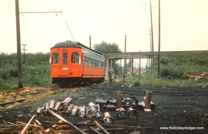 """#30 - EM: CAE 310 (Hicks, 1907) would appear to be on a fan trip about to go through the underpass between the Mannheim Road section and the Roosevelt Road section of the Mt. Carmel branch (aka the Cook County branch) which was used for freight operations only after 1926. Notice the trolley pole is up. This branch was unique in that it had no third rails anywhere from Mt. Carmel cemetery to where it joined the main line. view is looking NE. AK: Cook County Branch south of IC underpass north of Roosevelt with a charter. WS: Fantrip on Mt Carmel Branch. IC Iowa Division is overhead. Bill Shapotkin writes, """"The date of the photos (and there were several) of car #310 on a fantrip on the Mt Carmel Branch was (per caption on Pg 75 of SUNSET LINES (Vol1)) August 8, 1954."""""""