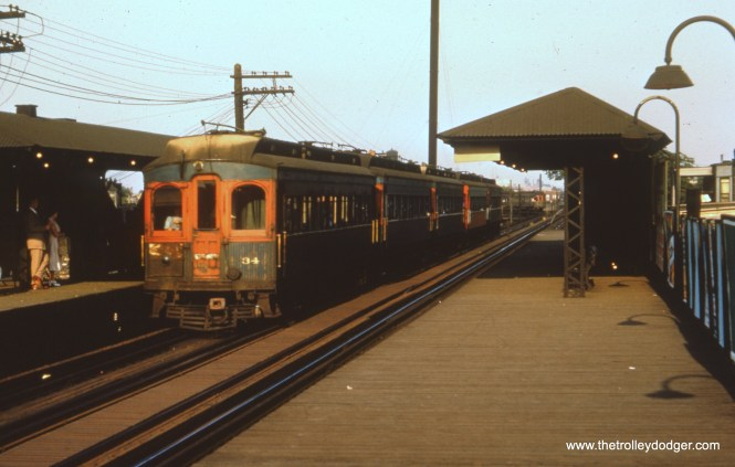 """#40 - FH: Nice shot of a five-car rush-hour train of """"shorties"""" at Kedzie, express to Wheaton if the sign is to be believed. The 34 is still in tattered blue and retains its light grey roof, or what's left of the paint anyway; a lot of cars had their roofs tarred in the late 1940s/early 1950s. It looks like the motorman has drawn the curtain over the """"railfan window"""" in the bulkhead so that the commuters don't all have the sun in their faces. And it's tough to tell but it looks like an ex-North Shore wood car in the background on the curve."""