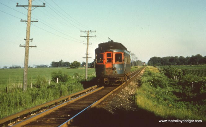 """#62 - JN: Batavia bound car having departed from Batavia Jct. (in distance). EM: CAE 141, a car obtained second hand from the North Shore Line travels through the middle of nowhere, I would guess on the Batavia branch. Bob Campbell says, """"141 is on the Aurora branch; not Batavia branch. West of Batavia Jct. was tangent on the Aurora branch. Batavia line just west of BJ was on a curve (see photo #66)."""" Bill Shapotkin writes, """"While not disputing that this photo is taken on the Batavia Branch, the remark: """"car having departed from Batavia Jct. (in distance)"""" I believe is incorrect. The reason I say that is that upon departing Batavia Jct (enroute to Batavia), the line IMMEDIATELY goes through a long sweeping curve to the N/W (as can be see in Photo 58). While I do not know exactly where this photo was taken, be assured that the distant station in photo is NOT Batavia Jct. By the way, this is NOT """"pull-in"""" trip of the Batavia car (enroute to Wheaton after the PM rush). If it were, the platform of Batavia Jct would be to the right (not to the left). I believe the photo is at either one of two locations: 1. A point JUST north of Bilter Rd (as the State Rd station would be on west side of R-O-W), or 2. A point JUST N/W of the sweeping curve out of Batavia Jct -- approx where East-West Tollway intersects the line today (thus station in distance is Bilter Rd (which, like State Rd was located on west side of R-O-W). In either case, believe this is a morning photo (of an E/B car) and that we are facing geographically N/W."""""""