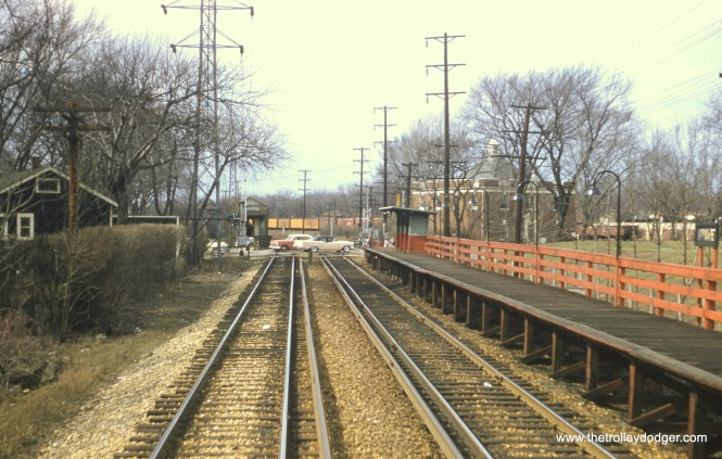 """#86 - JN: View west of 11th Ave. in Maywood EM: Station at 11th Av. in Maywood. The red railings show that this is a late picture, since they were painted green when the CTA trains of the Westchester branch stopped here for the last time December 8, 1951. Notice the newer automobiles crossing 11th Av. Dan Cluley adds, """"the cream colored convertible is a 1957 Olds. So given the bare trees this must have been taken in the Winter or early Spring of '57."""""""