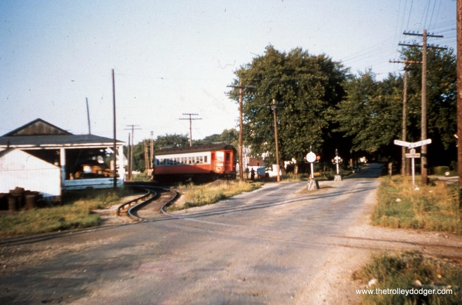 """#88 - JN: Westbound train on Aurora branch at Childs St., Wheaton EM: Now this is truly a """"mystery"""" photo! The street crossing looks like something out of the 1920's, but the Pullman car is painted in the last livery! Someone else will have to explain this one! Bob Campbell writes, """"Agree Childs Street, Wheaton looking east."""""""