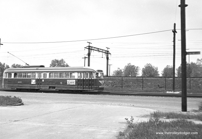 """CTA 4049 on that section of Cottage Grove that ran parallel to the Illinois Central electric suburban service (now Metra). The ad of the side of the PCC, advertising the Mickey Spillane film """"The Long Wait,"""" currently playing at the Woods Theater, dates this photo to between about May 19 and June 14, 1954."""