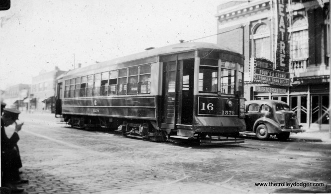 """Another view of a Lake Street car at the west end of the line, at Lake and Austin, in September 1939. Car 1579 is parked in front of the Park Theatre, this time showing a double feature of Four's a Crowd and Stronger Than Desire. Meanwhile, it looks the the motorman and conductor are taking a break at curbside. The Park is still advertising that it shows """"Talkies,"""" which became popular in 1927, and the sign that says """"Refrigeration"""" means that the theatre was already air-conditioned. The streetcar is working through-route 16 and is signed for State-79th."""