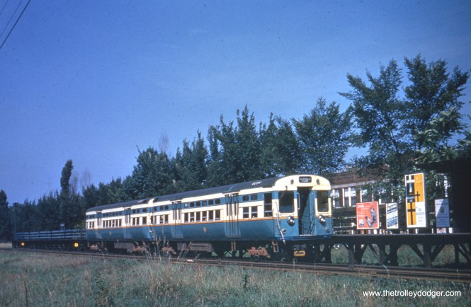 "A two-car train of ""flat door"" 6000-series cars at the ground-level Oak Park Avenue station on the Garfield Park ""L"" in the 1950s. These used PCC technology and were built with all new parts, unlike the later curved door cars that were partly built with parts salvaged from PCC streetcars. The building at rear, located at approximately 814 Harrison Street, is still standing in Oak Park. Sean Hunnicutt adds, ""That's 6053-54."""