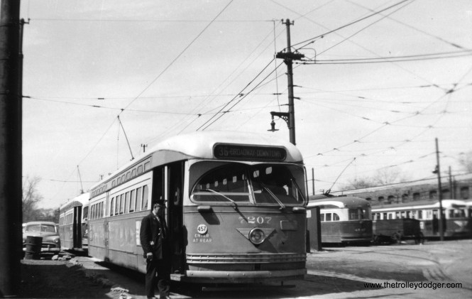 "CTA 7207 at Schreiber and Clark. Half the car barn lacked a roof due to a fire in the early 1920s. This photo probably dates to circa 1955-56 due to the presence of a prewar car at rear, which would have been used on route 49 - Western. 7207 had a scrap date of July 30, 1958, meaning it lasted until the end of Chicago streetcar service on June 21st of that year. The ""Enter at Rear"" sign means this car was still being used as two-man, with a conductor. (Railway Negative Exchange Photo)"