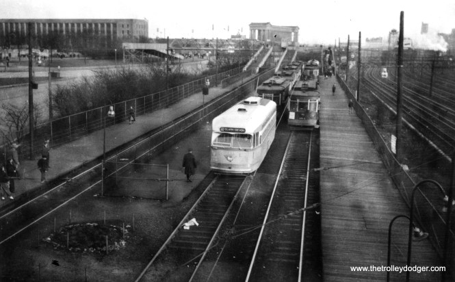 CTA 7116, built by St. Louis, at the Museum Loop. The Field Museum of Natural History would be off to the left, as is Lake Shore Drive. At rear, we can see the old Chicago Park District headquarters and Soldier Field. This loop was built to bring large numbers of visitors to A Century of Progress in 1933, Chicago's second World's Fair. The Illinois Central suburban electric tracks are at right. The streamlined moderne Park District building was built as the headquarters of the World's Fair administration. Unfortunately it was demolished as part of the project to renovate Soldier Field. (Railway Negative Exchange Photo)