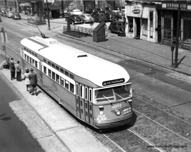 """Riders are about to board via the rear on postwar PCC 4257, """"Another New CTA Streetcar,"""" southbound at State and Roosevelt in 1948."""