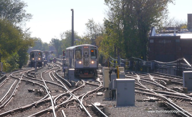 A Yellow Line train prepares to head north from the pocket, while a Purple Line train approaches.