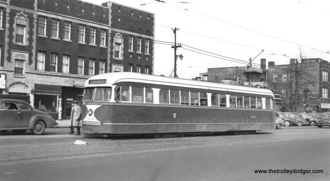 """CSL 7014 is westbound on the wider, outer end of Madison Street in this 1940s view. The auto at left is a type referred to as a """"business coupe,"""" a two-door car with a small back seat and a large trunk-- the type of car favored by salesmen of the 1940s. (Joe L. Diaz Photo)"""