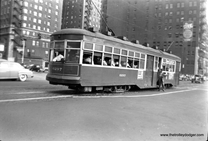 "CTA 6297 stops to let off passengers just south of the Loop. The sign advertising the Stevens Hotel should provide a clue as to the location. This is now the Hilton Chicago, located at 720 S. Michigan, but of course no streetcars ran on Michigan downtown. (The second trolley pole you see at rear is on another streetcar that is hidden from view by this one.) M. E. writes, ""These cars, called Sedans, ran on Cottage Grove Ave., sometimes in conjunction with the pre-war PCC cars. The Cottage Grove route downtown used Wabash Ave. Now let's talk about the big buildings. The two big buildings at the left are the back side of the Stevens Hotel, which fronted on Michigan Ave. The sign advertising the Stevens Hotel is on a separate building along Wabash. Another factor is the intersecting street, which must be Balbo (700 South). Balbo ran along the north side of the Stevens Hotel. Ergo, this picture is at Wabash and Balbo, facing southeast, and the streetcar is southbound."""