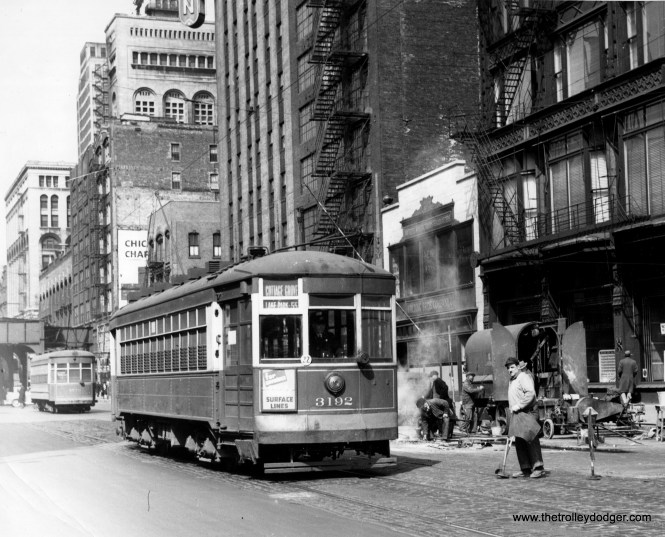 "CSL 3192 is heading south on Wabash on route 4 - Cottage Grove. We are just south of Harrison. The building to the right of the streetcar has an interesting ironwork facade. It is now the Leviton Gallery, and is located at 619 S. Wabash. Jeff Wien adds, ""CSL through Route Number 1 was BROADWAY-COTTAGE GROVE which terminated at Lake Park and 55th. CSL Route 4 was COTTAGE GROVE and it terminated at Cottage Grove and 115th. Prior to the CTA, many of the cars ran without route numbers, just route names and destinations. Since car 3192 is signed up to go to Lake Park & 55th, I would say that it is a Route 1 car, not a Route 4. I realize that I am being very trivial on this point. Meanwhile, the streetcar behind it is a Nearside which would be running on Route 4 Cottage Grove."""