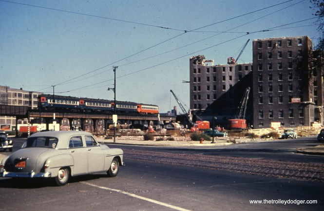 """The coming of summer also means more construction and demolition projects. A four-car CA&E train is seen on the old CTA Garfield Park """"L"""" at Ogden on October 19, 1952. Demolition of buildings for the Congress Expressway is well underway."""
