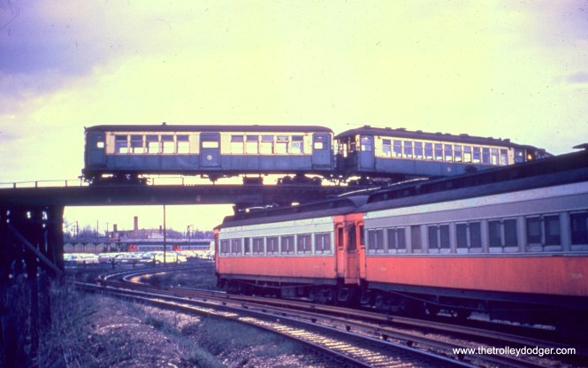 "A couple of CA&E woods (including 308) head east, approaching the Des Plaines Avenue terminal in April 1957, a few months before abandonment of passenger service. Another CA&E train is in the terminal, while a train of CTA 4000s, including a ""baldy"" with the blocked-off center door, turns around on a wooden trestle. This arrangement began when the CA&E stopped running downtown in September 1953."
