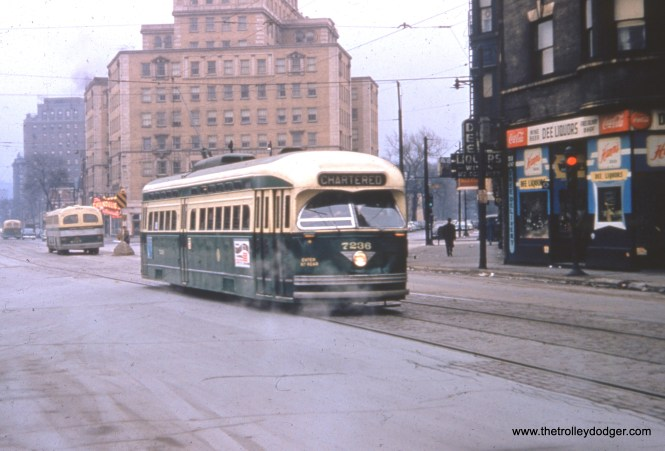 """CTA postwar PCC 7236 is shown northbound at Clark and Armitage on Sunday, December 18, 1955 in fantrip service. It was preferable in this period to run fantrips on weekends, since regular service on these lines was now being operated by buses, such as the ones shown in the background. We have run three other photos from this same fantrip in previous posts. Red car 225 was used ahead of this car. Since the trip organizers had advertised that car 144 would be used, they put a piece of oilcloth with that number on it over the Pullman's actual number. I also wrote about this same trip in the post The Old Math (144 = 225) March 13, 2013 on the CERA Members Blog. At that time, I thought the date of the trip was 1956, but a variety of sources since then say it was actually 1955. George Foelschow adds, """"The tan building directly behind the car is the North Park Hotel, the apex of the Old Town Triangle, site of the Chandelier Room, where I cast my first vote in 1960, since I lived just south of there on Lincoln Avenue. Sadly, the streetcars and trolley wires were gone by then, and only the tracks remained for a time."""""""