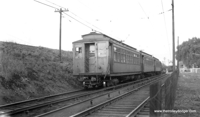 """Here, we see some Met cars in service on the Lake Street """"L"""". In the days when the outer portion ran on the ground, there was a short stretch just west of Harlem Avenue, which is what we see here. There was actually a station just west of Harlem, which was not used very much, compared to the one at Harlem and Marion. Wood cars last ran on Lake on July 5, 1954. In 1962, the nearby embankment was expanded by CTA to create a new yard. (Joe L. Diaz Photo, George Trapp Collection)"""