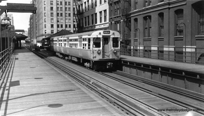 "This photo is rather curious, as a blow-up on the section behind CTA 6097-6098 (a Douglas Park train) appears to show tracks leading off to the right. That could possibly be the track connection, used from 1955-58, that ran through the old location of Wells Street Terminal. On the other hand, Myron Moyano says, ""the shot was taken from the LaSalle and Van Buren platform, looking west towards the junction at Wells and Van Buren. The platform furthest away after the junction was Franklin Street."" George Trapp adds, ""6097-6098, photo is at LaSalle and Van Buren, Insurance Exchange Building is above car 6097 and rear half of 6098. Junction is with Wells Street leg of Loop ""L"" and station in distance is Franklin and Van Buren used by Met trains."" He guesses the photo dates to about 1952. (Allen T. Zagel Photo, George Trapp Collection)"