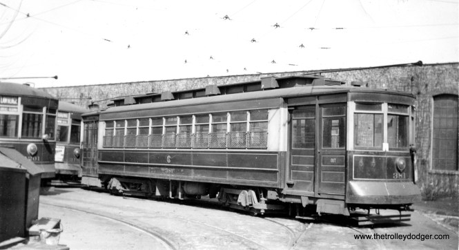"""CSL 381. Andre Kristopans: """"Probably somewhere in Devon Carbarn yard. Lawrence and Broadway/Wabash both ran out of there."""" George Trapp adds, """"I am pretty sure the location is at the Devon Depot, the east end of the South open yard, the ladder track curves out into Schreiber Avenue behind the photographer. Car 381 is signed for Cottage Grove-Broadway TR#1. Car 3201 to it's left is signed for Lawrence which operated out of Devon in the 1930's, it is one of the two original MU cars, 3200-3201 with 4 motors. These cars operated on Broadway during the daytime as two man cars and as night cars on Lawrence as one man. The car barn structure also looks like Devon Depot."""""""
