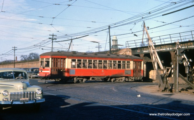 "CTA 3153 is turning from Pine onto Lake Street in January 1952, crossing ground-level tracks of the Lake Street ""L"". These were elevated onto the nearby embankment in 1962."
