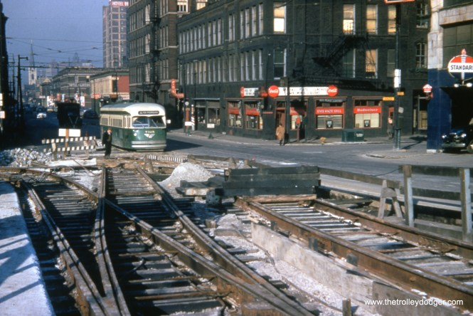 In the 1950s, CTA PCC 7125 is heading southbound at State and Kinzie while track work is underway nearby.