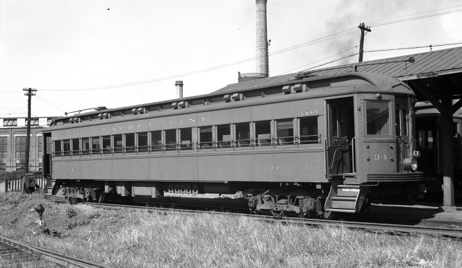 """Here is Lackawanna & Wyoming Valley (better known as the Laurel Line) car 34 at the Scranton (PA) station on September 21, 1941. Don's Rail Photos says, """"34 was built by Osgood-Bradley Car Co in 1924. It was sold to John C Bauman in 1953 and scrapped in 1956."""" The question has been raised in the past, as to whether the Laurel Line fleet, retired in the early 1950s, could have been any use to the Chicago, Aurora & Elgin, which needed to replace their wood cars with steel. It would appear that these cars were too long for the CA&E and would have needed modification. However, such changes had been made in 1937-38 to eight ex-Washington, Baltimore & Annapolis cars, which were renumbered into the 600 and 700-series. What was lacking in 1953, unfortunately, was the will to keep operating and investing money in a railroad that management thought was worth more dead than alive."""
