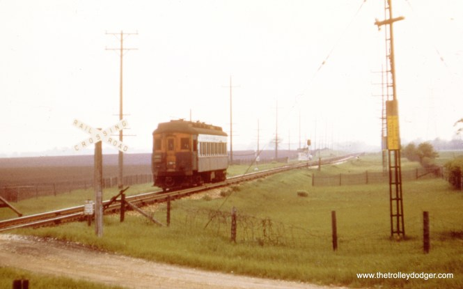 A single CA&E car on a single-track right of way, which could mean the Aurora, Batavia, or Elgin branches west of Wheaton.
