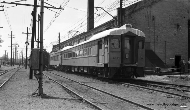 """Saturday afternoon, May 24, 1958: eastbound South Shore Line passenger train #109 at head end; has a silver roof. Michigan City, Ind."" The occasion was a Central Electric Railfans' Association fantrip, using Illinois Central Electric cars on the South Shore Line. The IC train is just visible behind some poles in the center of the picture. (Robert Selle Photo)"