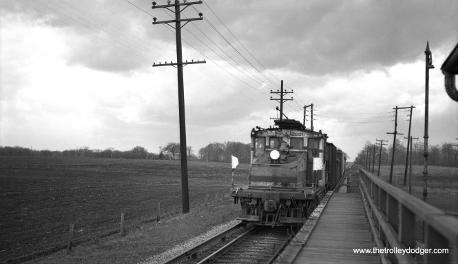 """CA&E freight train headed by loco 2001, to Wheaton from Aurora (taken at Batavia Junction), Saturday noon, April 25, 1953."" Notice all the platform extensions here have been turned up to provide the train with enough clearance to pass. They were flipped down for use by passenger trains. (Robert Selle Photo)"