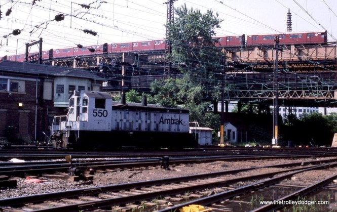 """I wanted to include this photo in spite of the fact that the subject is Amtrak SSB-1200 #550 at Q Tower at Sunnyside, Queens, New York. I hope it will be of interest to traction fans because of the IRT subway train of NYCTA R-36 """"Redbirds"""" passing overhead in the background. 6-20-87."""