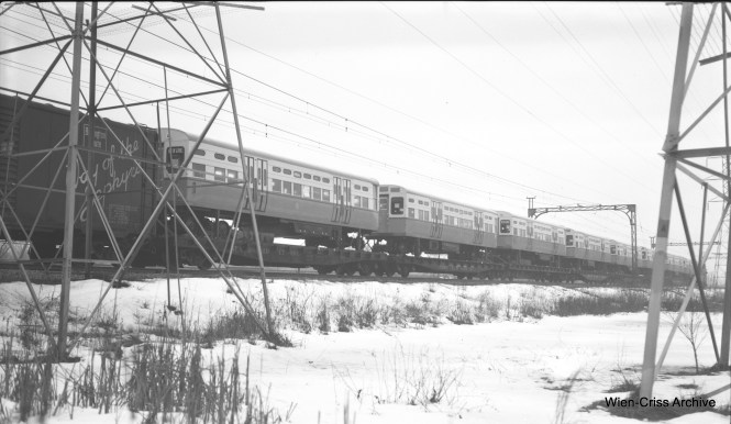 "A view of the first 6400-series CTA ""L"" cars head into Chicago on a North Shore Line freight train on February 19, 1955. The location is just south of the Highmoor, Illinois station. Some of the parts used on these cars were recyycled from scrapped CTA PCCs that had less than 10 years' service. (Robert Selle Photo, Wien-Criss Archive)"