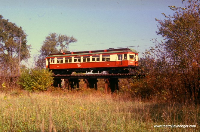 "Waterloo, Cedar Falls & Northern car 100 on the Southern Iowa Railway on October 13, 1963. Don's Rail Photos: ""100 was built by McGuire-Cummings in 1914. It was built as a second motor to operate behind the 140s as a two car train. The baggage compartment was a kitchen, and the rear end was an open platform observation. The buffet section was replaced with coach seats in 1918. The car was then rebuilt with a control station and baggage compartment in 1928 and the rear platform was enclosed at that time. It was the last interurban left on the WCF&N when it became diesel freight, and it was donated to the Iowa Chapter of the NRHS in 1956. It was moved to Centerville and operated on the Southern Iowa Ry. When the SI cut back its operation and dieselized, the Iowa Chapter transferred the car to the Iowa Terminal RR in 1966. Shortly after it was repainted and put into charter service, it was destroyed in the carbarn fire early November 24, 1967. It had been the only car saved from the WCF&N roundhouse fire on October 31, 1954, when the other two cars of its class burned."" This slide has ""Q transfer"" noted on it-- not sure what that means. (James J. Buckley Photo)"