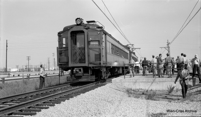 "On May 24, 1958 the Central Electric Railfans' Association operated a fantrip on the South Shore Line, using Illinois Central equipment. Normally, South Shore cars ran on the IC, but not the other way around. Here, they are having a photo stop at the ""new"" East Chicago station, parallel to the Indiana Toll Road, which opened in 1956. It replaced street running in East Chicago. The view looks east. (Robert Selle Photo, Wien-Criss Archive)"