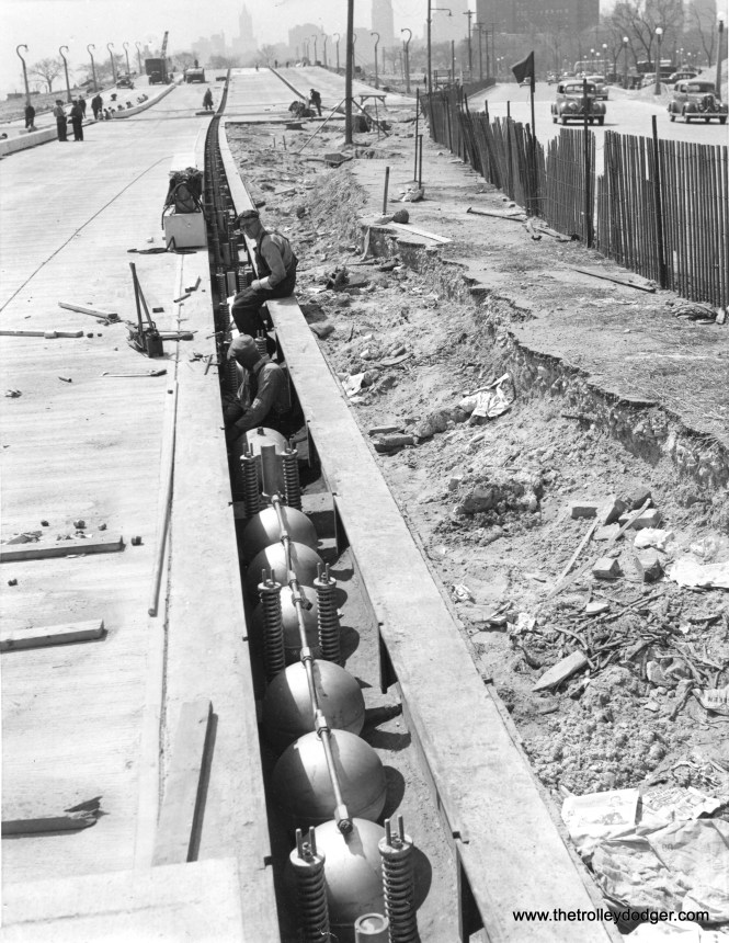 """While Chicago's Congress expressway (now the Eisenhower) is rightly considered its first, Lake Shore Drive preceded it as an """"almost"""" expressway. Here. we see construction taking place on December 13, 1940. Until the early 1970s, LSD had lanes that could be reversed in rush hour by raising and lowering these short barriers. Unfortunately, this resulted in a number of head-on collisions, and these were eventually deactivated. The photo caption reads, """"Workmen install line of elevating curbs in new express highway on Chicago's lake front. The curbs, placed two lanes apart on the eight lane roadway, give extra lanes to rush hour traffic to ease traffic flow. The elevating jacks shown raise the curb to height of nine inches, exert pressure of 12 tons. The retracting springs, having a 10-ton pressure, pull the curbs down when the hydraulic jacks are released. The entire curb system is operated from one central control station."""" (Photo by Acme)"""
