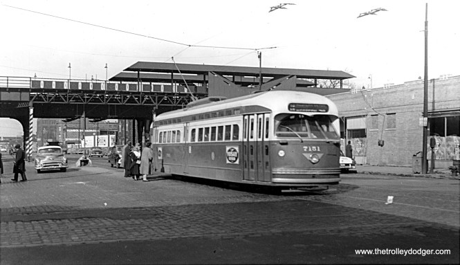 """CTA PCC 7151, a product of St. Louis Car Company, heads south on Route 49 - Western at North Avenue in 1953. The """"L"""" station behind it was part of the Humboldt Park branch, which was abandoned in 1952. Once the station was closed, signs advertising """"L"""" service were removed although I don't believe this portion of the structure was removed until the early 1960s. Note that riders at this safety island are boarding at the rear, as this is a two-man car."""