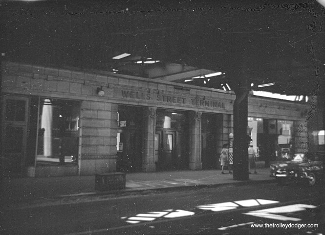 """Here's a rather unique view showing the front of the old Wells Street Terminal, or what was left of it anyway, as it appeared in 1959. This terminal was last used by the CA&E in 1953. Two years later, the upper portion of the attractive facade was removed and a new track connection was built so that Garfield Park trains could connect to the Loop """"L"""". A new connection was needed, since the old one had to give way to construction on Wacker Drive. The remainder of the terminal, and the track connection, were no longer needed after the Congress rapid transit line replaced the Garfield Park """"L"""" in 1958, and they were removed in 1964. Note there is a barber shop occupying part of the building."""