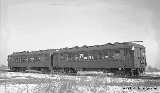"""This negative did not come with any identifying information, but it is obviously from a February 12, 1939 fantrip where the fledgling Central Electric Railfans' Association chartered Chicago Rapid Transit Company """"L"""" cars 4317 and 4401 and took them out on parts of the CA&E including the Mount Carmel branch. However, since that line used overhead wire, that's not where this picture was taken. Instead, it appears to be out near the end of the line at Mannheim and 22nd Street on the CRT's lightly used Westchester line, which was built in anticipation of housing being built in this area (which did not come about until the 1950s). South of Roosevelt Road, the line was single-track, which appears to be the case here. If not for the Great Depression, more housing would have been built here. We have previously run two other pictures from the same fantrip, both taken on the Mt. Carmel branch. The CTA substituted bus service for """"L"""" on the Westchester line in 1951 as it did not want to continue paying rent to the CA&E, which had already announced its intentions to truncate passenger service to Forest Park, which meant similar rent payments to the CTA were about to cease."""