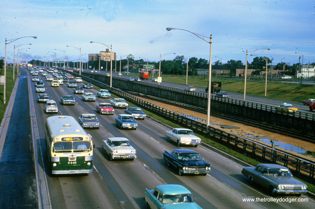 "CTA 5445 is heading west on the Congress (now Eisenhower) Expressway in the mid-1960s, on its way toward DesPlaines Avenue, eastern terminus of Route 17 - Westchester. This was the bus line that replaced the old Westchester ""L"" in 1951. Service was gradually shifted to PACE Route 317 between 1992 and 2012. The CTA rapid transit line, at right, goes into the Lotus Tunnel just west of here, and shifts out of the median."